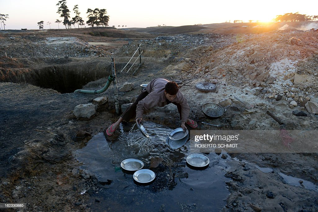 In this photograph taken on January 29, 2013, a miners washes dishes used by him and other miners who live in a hut near mine shafts that dot the hills near Mulang village in the Indian northeastern state of Meghalaya. Thousands of private mines employ slim men and boys that will fit in thin holes branching out from deep shafts dug out from the ground in the East Jaintia Hills in Northeastern Indian state of Meghalaya. This state is the only state in India where coal mining is done privately by mine owners, who use cheap labour to supply the demand for this energy resource. Accidents and quiet burials are commonplace, with years of uncontrolled drilling making the rat-hole mines unstable and liable to collapse at any moment. After decades of unregulated mining, the state is due to enforce its first-ever mining policy later this year. AFP PHOTO/ Roberto Schmidt