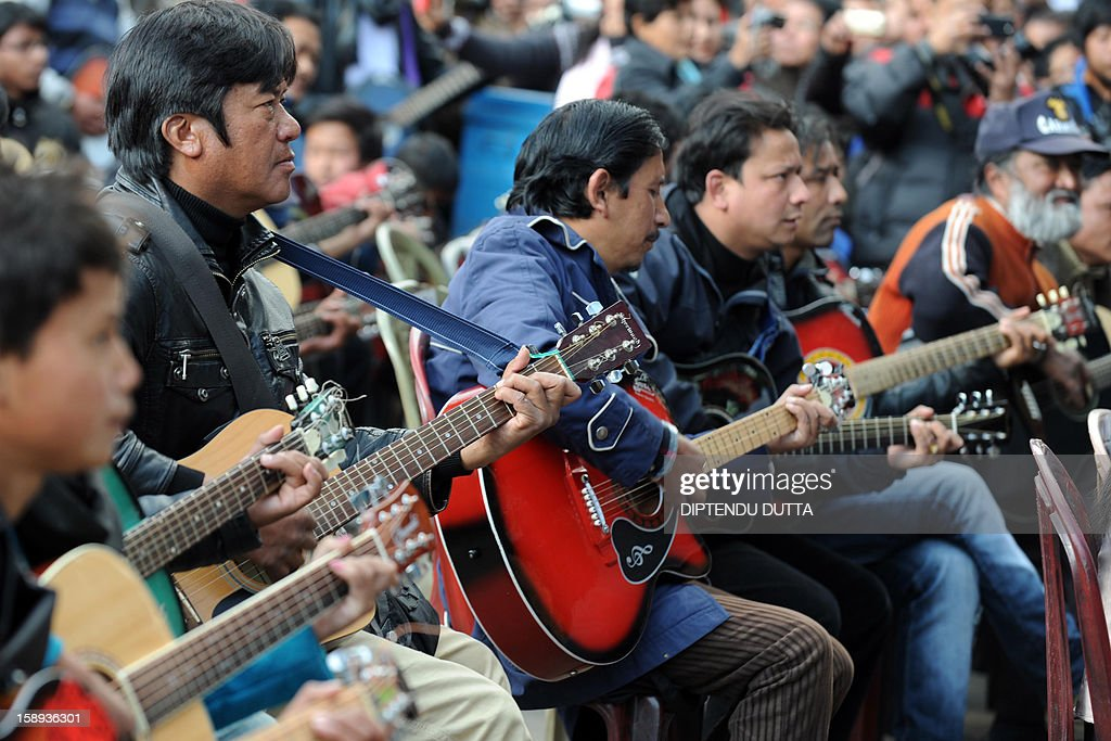 In this photograph taken on January 3, 2013, musicians play John Lennon's 'Imagine' in a memorial tribute to the 23-year old Indian gang rape victim, during a mass guitar ensemble played by some 600 guitarists in Darjeeling. A group of 600 guitarists have paid a musical tribute to an Indian gang-rape victim, playing 'Imagine' by John Lennon in a bid to spread 'hope, peace and promise' in a country still coming to terms with the violence. AFP PHOTO/Diptendu DUTTA