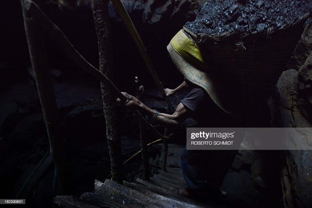 In this photograph taken on January 30, 2013, a miner carries a load of about 70 kg of wet coal on his back as he slowly makes his way up makeshift stairs inside a 50 meter deep mine shaft near Rymbai village in the Indian northeastern state of Meghalaya. Thousands of private mines employ slim men and boys that will fit in thin holes branching out from deep shafts dug out from the ground in the East Jaintia Hills in Northeastern Indian state of Meghalaya. This state is the only state in India where coal mining is done privately by mine owners, who use cheap labour to supply the demand for this energy resource. Accidents and quiet burials are commonplace, with years of uncontrolled drilling making the rat-hole mines unstable and liable to collapse at any moment. After decades of unregulated mining, the state is due to enforce its first-ever mining policy later this year. AFP PHOTO/ Roberto Schmidt