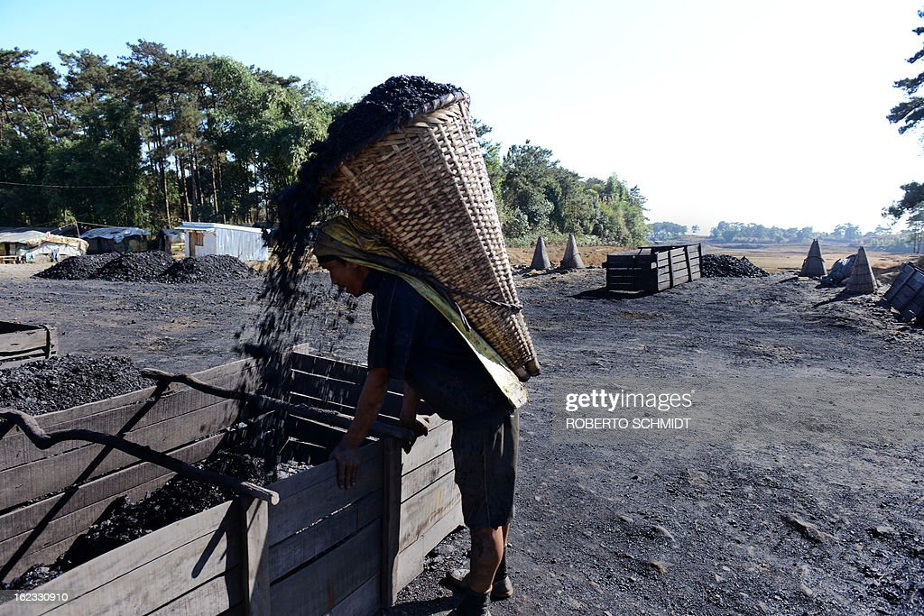 In this photograph taken on January 30, 2013, a miner unloads his basket ladden with about 70 kg of wet coal that others scraped in tunnels in the East Jaintia Hills district of the Indian northeastern state of Meghalaya. Thousands of private mines employ slim men and boys that will fit in thin holes branching out from deep shafts dug out from the ground in the East Jaintia Hills in Northeastern Indian state of Meghalaya. This state is the only state in India where coal mining is done privately by mine owners, who use cheap labour to supply the demand for this energy resource. Accidents and quiet burials are commonplace, with years of uncontrolled drilling making the rat-hole mines unstable and liable to collapse at any moment. After decades of unregulated mining, the state is due to enforce its first-ever mining policy later this year. AFP PHOTO/ Roberto Schmidt