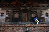 In this photograph taken on January 30 a Nepalese girl sit on the steps of a temple at Patan Durbar square in Lalitpur Patan Durbar Square a UNESCO...