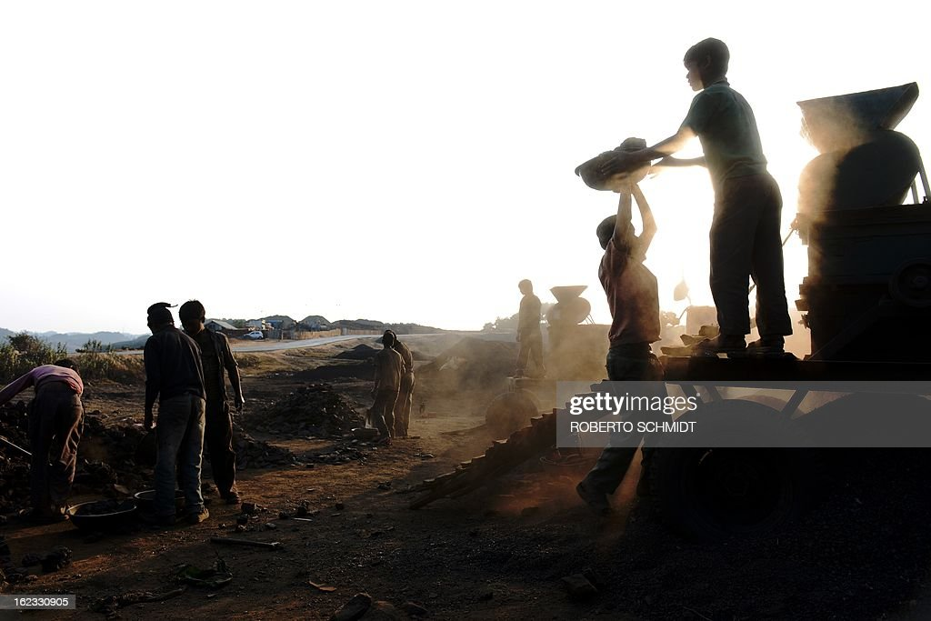 In this photograph taken on January 30, 2013, Indian children carry coal in baskets towards a coal crushing machine at a road side coal depot in the East Jaintia Hills district of the Indian northeastern state of Meghalaya. Thousands of private mines employ slim men and boys that will fit in thin holes branching out from deep shafts dug out from the ground in the East Jaintia Hills in Northeastern Indian state of Meghalaya. This state is the only state in India where coal mining is done privately by mine owners, who use cheap labour to supply the demand for this energy resource. Accidents and quiet burials are commonplace, with years of uncontrolled drilling making the rat-hole mines unstable and liable to collapse at any moment. After decades of unregulated mining, the state is due to enforce its first-ever mining policy later this year. AFP PHOTO/ Roberto Schmidt