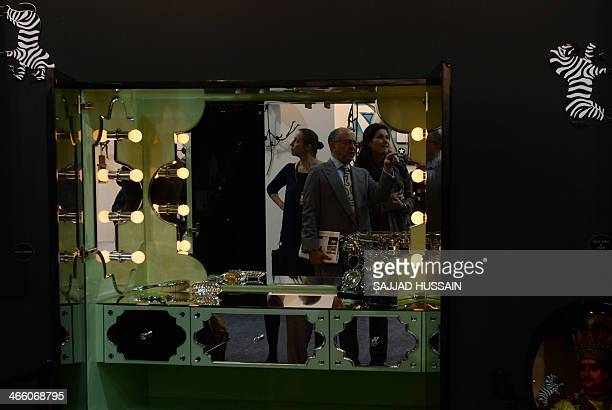 In this photograph taken on January 30 Indian visitors are reflected in the mirror of a dressing table during the India Art Fair in New Delhi The...