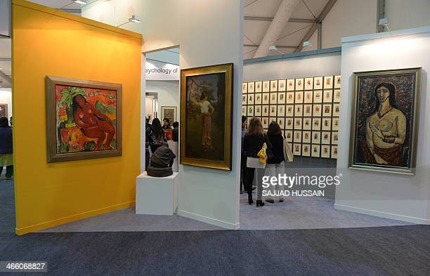 In this photograph taken on January 30 Indian visitors look at artwork on display during the India Art Fair in New Delhi The India Art fair has been...