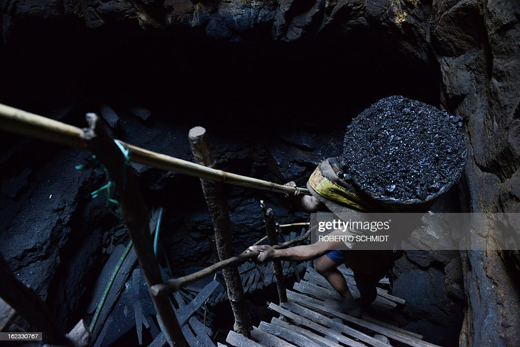 In this photograph taken on January 31, 2013, a miner slowly carries a heavy load of wet coal on a basket hundreds of feet up on wooden slats that brace the sides of a deep coal mine shaft near Rimbay village in the Indian northeastern state of Meghalaya. Thousands of private mines employ slim men and boys that will fit in thin holes branching out from deep shafts dug out from the ground in the East Jaintia Hills in Northeastern Indian state of Meghalaya. This state is the only state in India where coal mining is done privately by mine owners, who use cheap labour to supply the demand for this energy resource. Accidents and quiet burials are commonplace, with years of uncontrolled drilling making the rat-hole mines unstable and liable to collapse at any moment. After decades of unregulated mining, the state is due to enforce its first-ever mining policy later this year. AFP PHOTO/ Roberto Schmidt