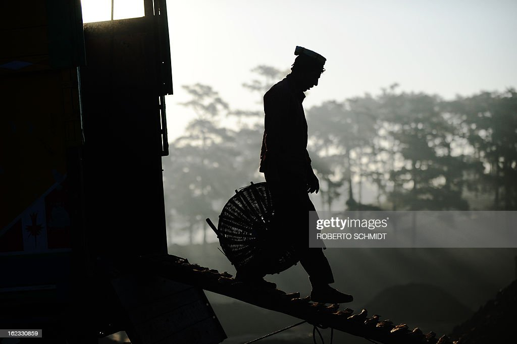 In this photograph taken on January 31, 2013, a miner walks off a truck after loading it with coal at a road side coal depot near Rymbai village in the Indian northeastern state of Meghalaya. Thousands of private mines employ slim men and boys that will fit in thin holes branching out from deep shafts dug out from the ground in the East Jaintia Hills in Northeastern Indian state of Meghalaya. This state is the only state in India where coal mining is done privately by mine owners, who use cheap labour to supply the demand for this energy resource. Accidents and quiet burials are commonplace, with years of uncontrolled drilling making the rat-hole mines unstable and liable to collapse at any moment. After decades of unregulated mining, the state is due to enforce its first-ever mining policy later this year. AFP PHOTO/ Roberto Schmidt