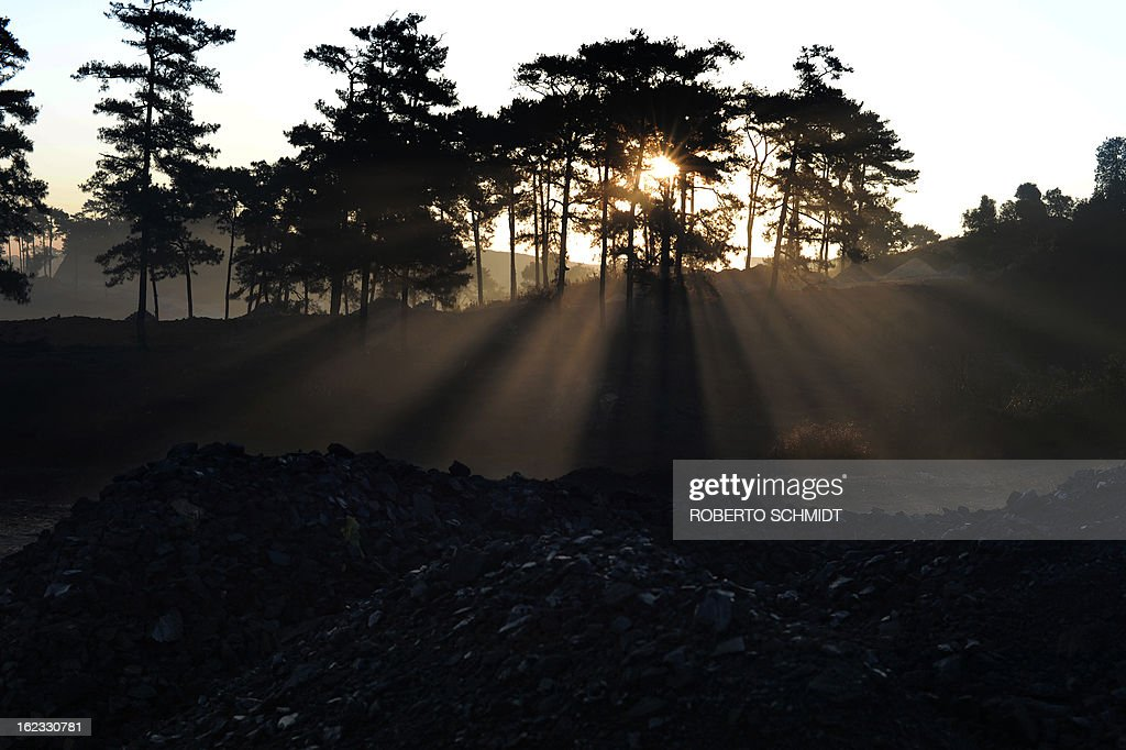 In this photograph taken on January 31, 2013, early morning light shines through trees on mounds of coal piled at a road side coal depot near Rymbai village in the Indian northeastern state of Meghalaya. Thousands of private mines employ slim men and boys that will fit in thin holes branching out from deep shafts dug out from the ground in the East Jaintia Hills in Northeastern Indian state of Meghalaya. This state is the only state in India where coal mining is done privately by mine owners, who use cheap labour to supply the demand for this energy resource. Accidents and quiet burials are commonplace, with years of uncontrolled drilling making the rat-hole mines unstable and liable to collapse at any moment. After decades of unregulated mining, the state is due to enforce its first-ever mining policy later this year. AFP PHOTO/ Roberto Schmidt