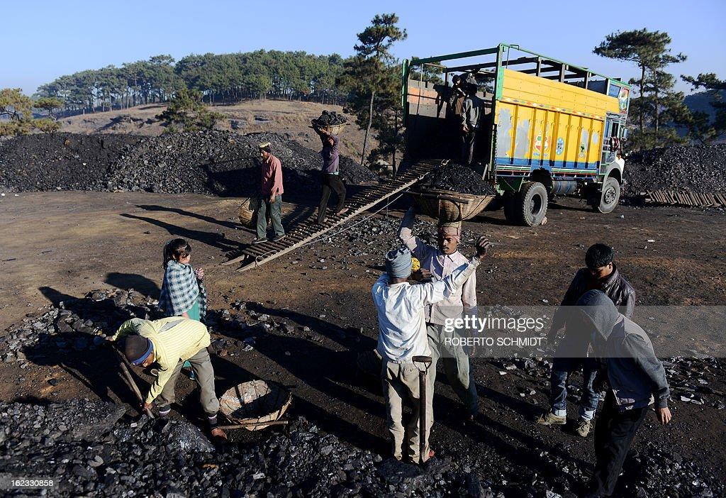 In this photograph taken on January 31, 2013, miners haul baskets full of coal as they load a truck with coal at a road side coal depot near Rymbai village in the Indian northeastern state of Meghalaya. Thousands of private mines employ slim men and boys that will fit in thin holes branching out from deep shafts dug out from the ground in the East Jaintia Hills in Northeastern Indian state of Meghalaya. This state is the only state in India where coal mining is done privately by mine owners, who use cheap labour to supply the demand for this energy resource. Accidents and quiet burials are commonplace, with years of uncontrolled drilling making the rat-hole mines unstable and liable to collapse at any moment. After decades of unregulated mining, the state is due to enforce its first-ever mining policy later this year. AFP PHOTO/ Roberto Schmidt