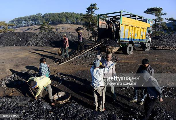 In this photograph taken on January 31 miners haul baskets full of coal as they load a truck with coal at a road side coal depot near Rymbai village...
