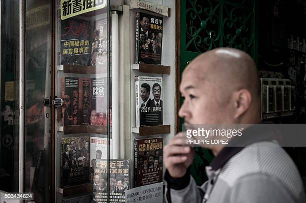 In this photograph taken on January 4 2016 a man stands by a book featuring Chinese President Xi Jinping and former Chinese political heavyweight Bo...