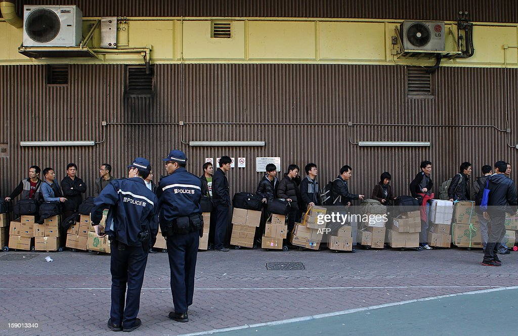 In this photograph taken on January 5, 2013, policemen watch as visitors from mainland China wait in a queue with their goods outside the Sheung Shui train station in Hong Kong. An influx of parallel traders in Hong Kong who purchase items tax-free such as baby milk formula, diapers, soft drinks and cosmetics and then resell it in mainland China at a profit is causing growing unrest with local residents who say retail prices are being driven up by the practice. AFP PHOTO / Dale de la REY