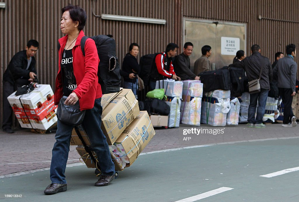 In this photograph taken on January 5, 2013, visitors from mainland China wait in a queue with their goods outside the Sheung Shui train station in Hong Kong. An influx of parallel traders in Hong Kong who purchase items tax-free such as baby milk formula, diapers, soft drinks and cosmetics and then resell it in mainland China at a profit is causing growing unrest with local residents who say retail prices are being driven up by the practice. AFP PHOTO / Dale de la REY