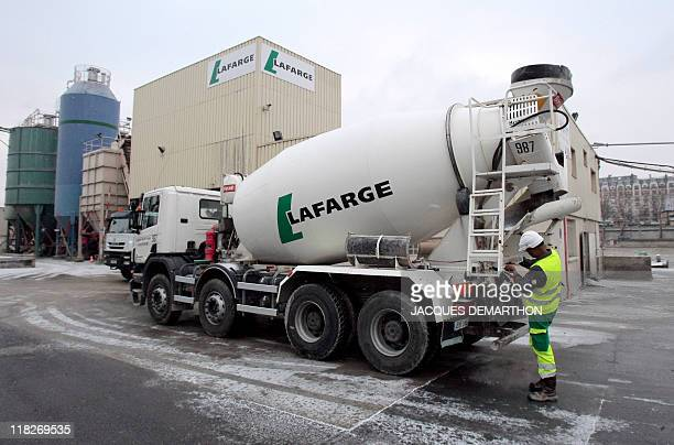 In this photograph taken on January 6 a French worker adjusts machinery on a cement mixing truck at a processing plant of Lafarge the world's largest...