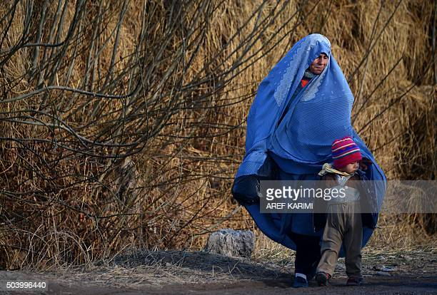 In this photograph taken on January 7 an Afghan burqaclad woman walks with a child along a street on the outskirts of Herat AFP PHOTO / AREF KARIMI /...