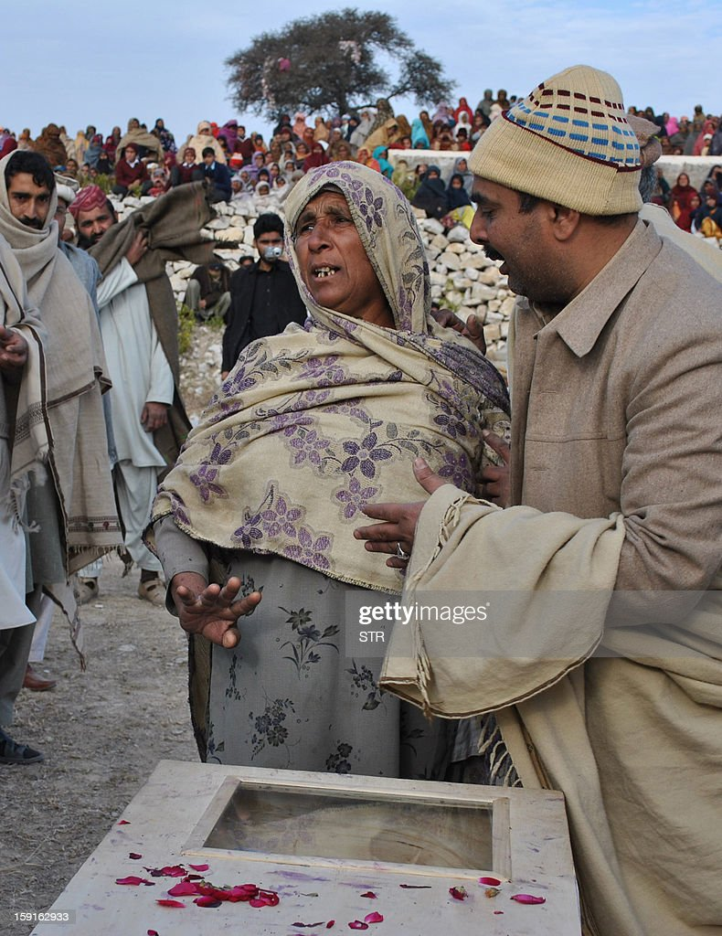 In this photograph taken on January 8, 2013, a mourner comforts the mother of Pakistani soldier Mohammad Aslam, who was killed during a border post attack in the Haji Pir sector of Pakistan-administered Kashmir by Indian soldiers, during his funeral in Khairpur village Chakwal district. Pakistani and Indian troops exchanged fire on January 6 along their hotly disputed border in divided Kashmir, with each side accusing the other of starting the clash. Pakistan on January 9 denied an Indian claim that its troops killed two Indian soldiers in a cross-border attack on January 8 that has raised tensions in South Asia, a military official said.