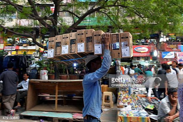 In this photograph taken on July 1 an Indian labourer carries boxes of computer terminals on his head as he walks through an electronics market in...