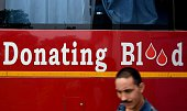 In this photograph taken on July 1 an Indian man walk past a blood donation bus at a camp organised by the Rotary Blood Bank in New Delhi Vinod...