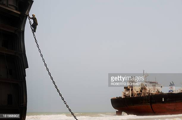 In this photograph taken on July 10 A Pakistani shipyard worker climbs an anchor chain securing a vessel beached and being dismantled at one of the...