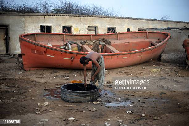 In this photograph taken on July 10 a shipyard worker pulls water from a well to wash himself at the end of his shift near rooms where he and other...