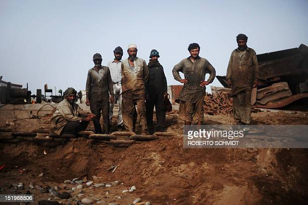 In this photograph taken on July 10 Pakistani shipyard workers wait to climb aboard a beached vessel being dismantled in one of the 127 shipbreaking...