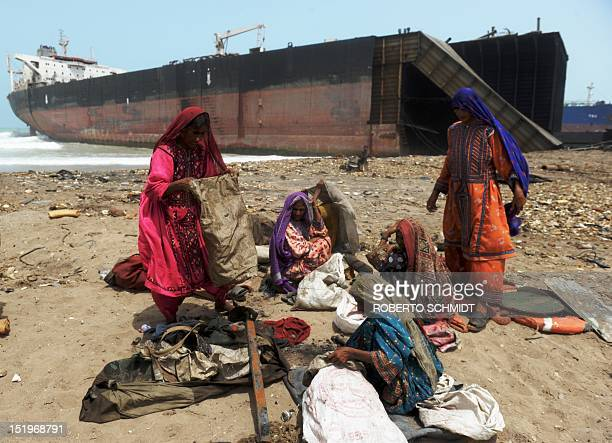 In this photograph taken on July 10 Pakistani women empty sacks with small scrap metal pieces they picked up on the shore near where vessel have been...