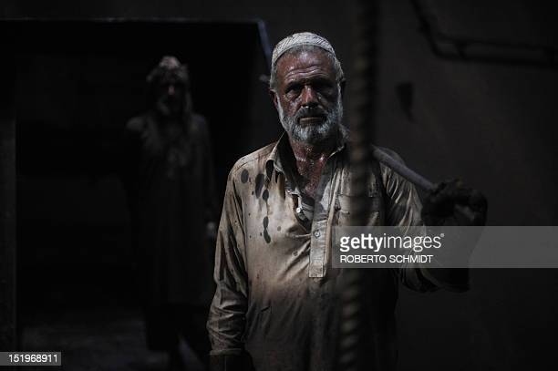 In this photograph taken on July 11 a Pakistani shipyard worker takes a break from clearing out the inside of the hull of a vessel beached and being...