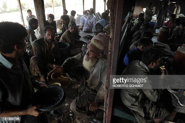 In this photograph taken on July 11 Pakistani men crowd a modest food kiosk offering lunch meals for a price to shipyard workers near one of the 127...