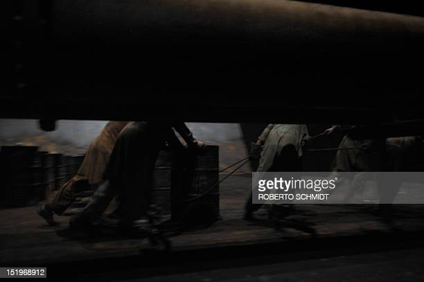 In this photograph taken on July 11 Pakistani shipyard workers remove oil barrels from inside the hull of a vessel beached and being dismantled at...