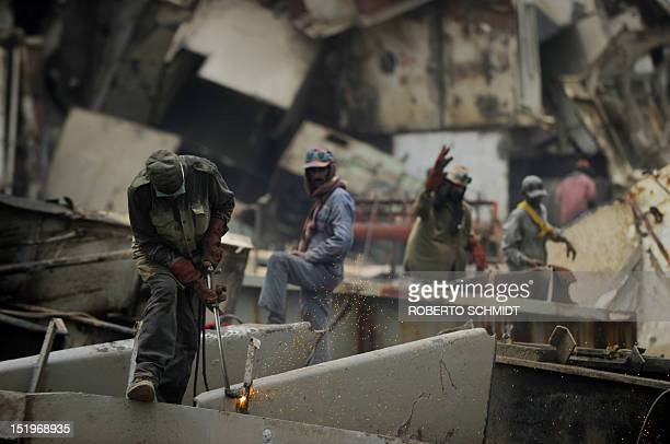 In this photograph taken on July 11 Pakistani shipyard workers use blow torches to cut up metal broken off vessels beached at one of the 127...
