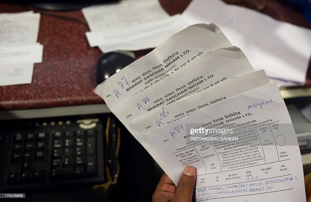 In this photograph taken on July 12, 2013, an Indian employee holds telegram applications at the Central Telegraph Office in Kolkata. Thousands of Indians crammed into telegram offices to send souvenir messages to friends and family in a last-minute rush before the service shuts down. July 14, 2013, is the last day that messages will be accepted by the 162-year-old service, the last major commercial telegram operation. In the days before mobile phones and the Internet, the telegram network was the main form of long-distance communication, with 20 million messages dispatched from India during the subcontinent's bloody partition in 1947. AFP PHOTO/ Dibyangshu SARKAR