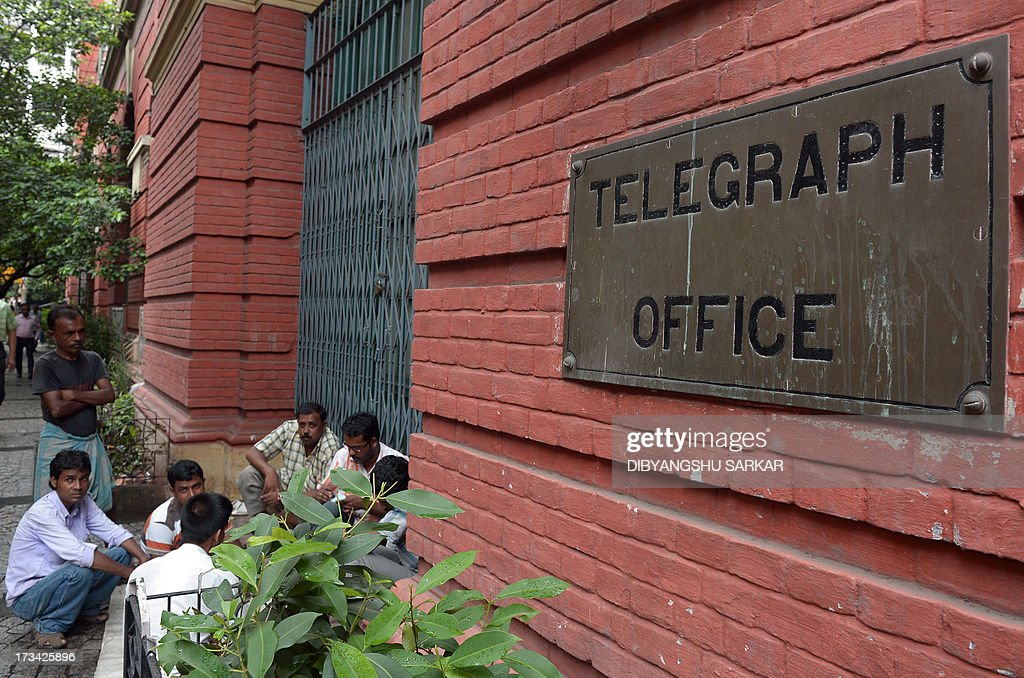 In this photograph taken on July 12, 2013, Indian pedestrians play cards at the closed doors of the Central Telegraph Office in Kolkata. Thousands of Indians crammed into telegram offices to send souvenir messages to friends and family in a last-minute rush before the service shuts down. July 14, 2013, is the last day that messages will be accepted by the 162-year-old service, the last major commercial telegram operation. In the days before mobile phones and the Internet, the telegram network was the main form of long-distance communication, with 20 million messages dispatched from India during the subcontinent's bloody partition in 1947. AFP PHOTO/ Dibyangshu SARKAR