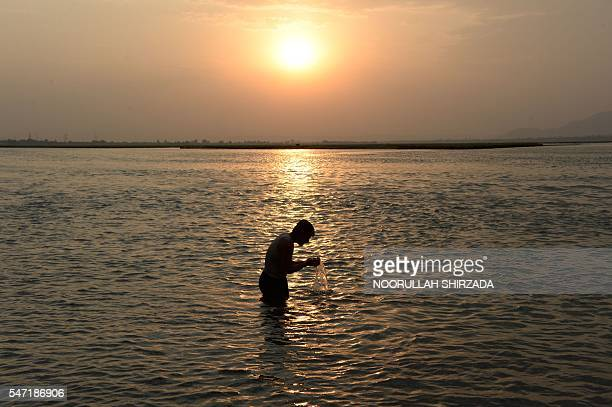 In this photograph taken on July 13 an Afghan man performs ablution before prayers in the Kabul river on the outskirts of Jalalabad / AFP / NOORULLAH...