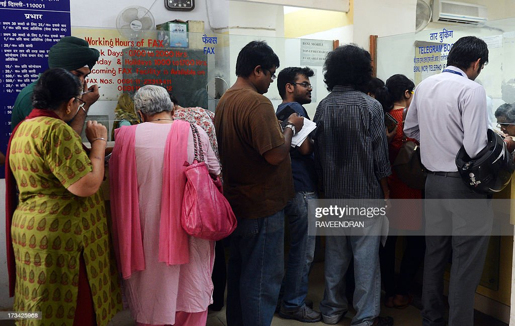 In this photograph taken on July 13, 2013, Indian customers line up in front of a telegraph booking counter to send a telegram in New Delhi. Thousands of Indians crammed into telegram offices to send souvenir messages to friends and family in a last-minute rush before the service shuts down. July 14, 2013, is the last day that messages will be accepted by the 162-year-old service, the last major commercial telegram operation. In the days before mobile phones and the Internet, the telegram network was the main form of long-distance communication, with 20 million messages dispatched from India during the subcontinent's bloody partition in 1947. AFP PHOTO/ RAVEENDRAN
