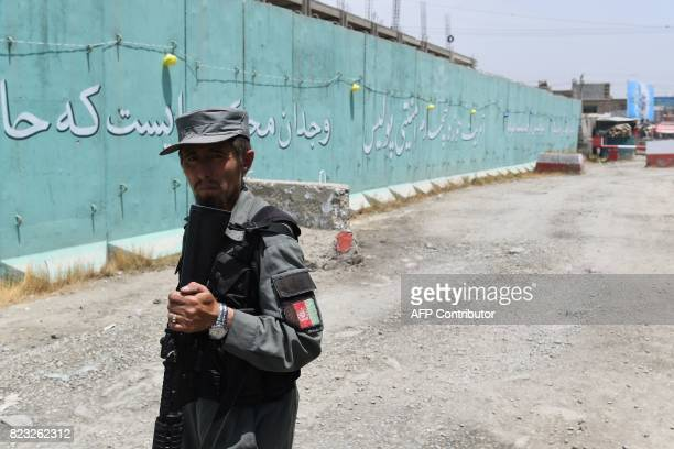 In this photograph taken on July 16 Afghan policemen keep watch near blast walls in Kabul The blast walls that cut through Kabul like ramparts are...