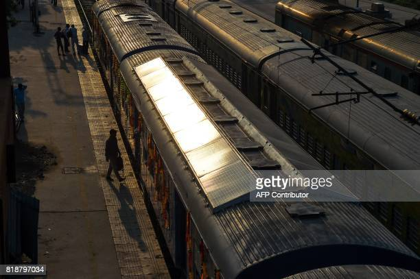 TOPSHOT In this photograph taken on July 18 2017 Indian commuters board the 1600 HP solarpowered DEMU train is seen parked at Sarai Rohilla railway...