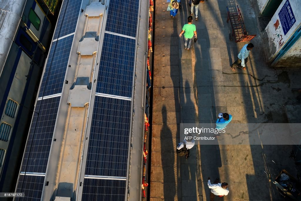 In this photograph taken on July 18, 2017 Indian commuters walk past the 1600 HP solar-powered DEMU (diesel electrical multiple unit) train is seen parked at Sarai Rohilla railway station in New Delhi. India has added solar panels to the roof of a train in a national first as it tries to reduce its massive carbon footprint and modernise its vast colonial-era rail network. The lighting, fans and information displays inside the train -- once powered by diesel -- will run off the sun's energy after the panels were fitted to the carriage. WITH 'INDIA-TRANSPORT-RAIL-CLIMATE-WARMING' BY