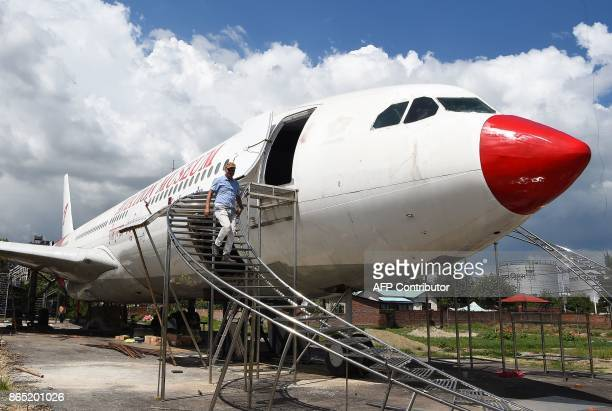 In this photograph taken on July 18 2017 Nepali pilot Bed Upreti walks from an airplane that has been converted into an aviation museum in Kathmandu...