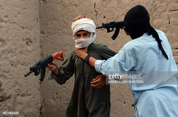In this photograph taken on July 18 Afghan children play with plastic guns as they celebrate the second day of Eid alFitr which marks the end of the...