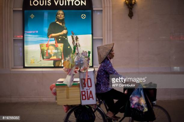 TOPSHOT In this photograph taken on July 19 a bicycle vendor offering her merchandise in the streets of Hanoi pedals past a high end merchandise mall...
