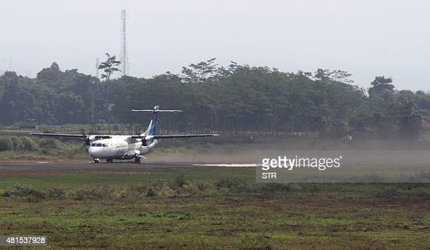 In this photograph taken on July 20 a Garuda Indonesia ATR 72600 passenger aircraft kicks up a cloud of dust which includes volcanic ash from Mount...