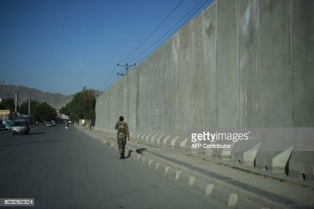 In this photograph taken on July 22 an Afghan National Army soldier walks past blast walls in front of the ruined Darul Aman palace in Kabul The...