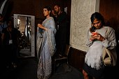 In this photograph taken on July 22 an Indian hair dresser stands on a chair as he gives the finishing touches to a model's hair ahead of the show by...