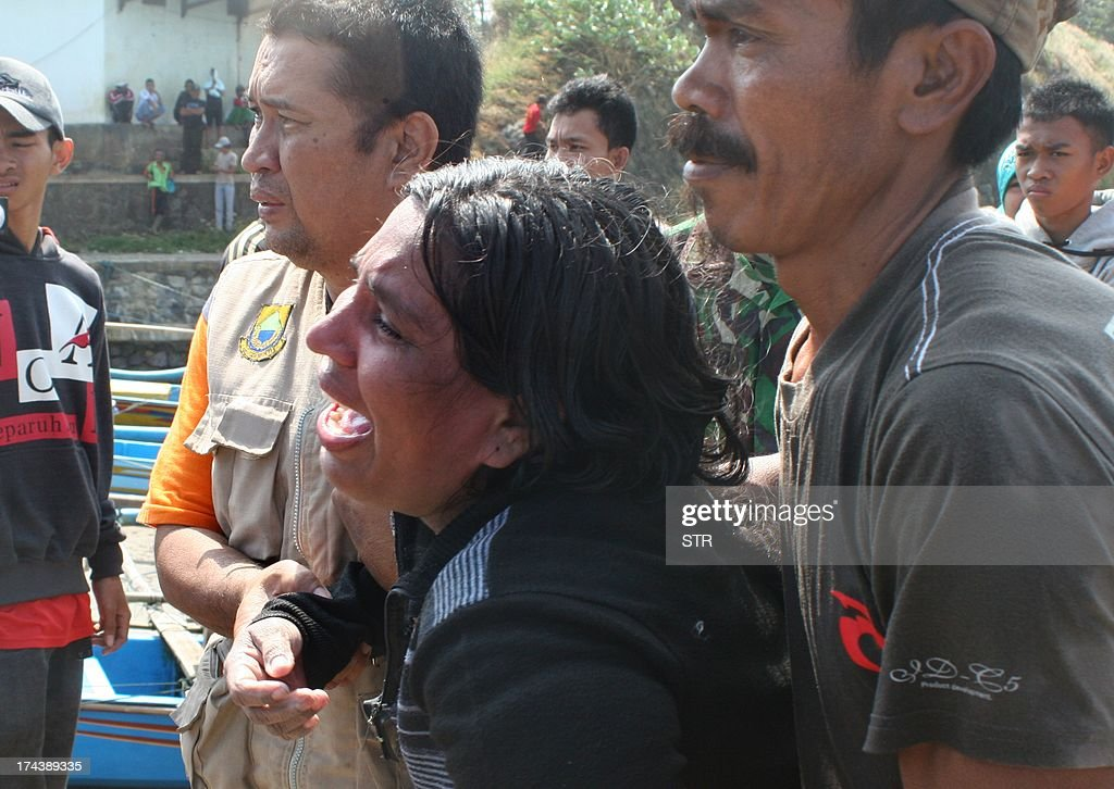 In this photograph taken on July 24, 2013 a female survivor (C) grieves while assisted by Indonesian rescuers upon her arrival at the wharf of Cidaun, West Java on July 24, 2013 after an Australia-bound boat carrying asylum-seekers sank off the Indonesian coast, leaving at 11 confirmed dead. Rescuers continued searching the seas off Indonesian for survivors. Police have said around 200 were aboard, but an asylum-seeker has said 250 people, mostly Sri Lankans, made the perilous journey. AFP PHOTO