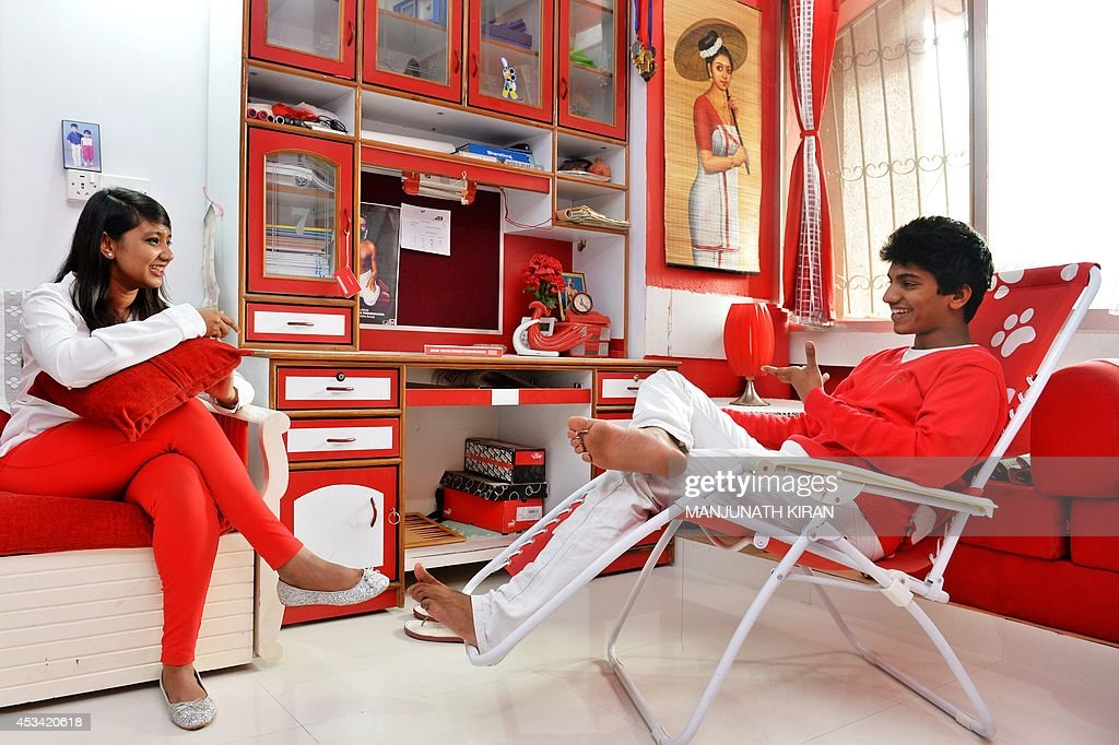 In this photograph taken on July 26, 2014,, 16-year-old Maneesha (L) and 18-year-old Bharath Raj, the children of Indian businessman Sevenraj , who has a fixation for the colours red and white, share a conversation in the family's residence in Bangalore. 52-year-old Sevenraj's fetish for red and white colours started several decades ago with an intention to create a unique identity for himself and a brand image for his real estate agency went on to become a part and parcel of his life, his home and his family. Born as the seventh offspring, his realist father named him 'Sevenraj' and thus the number '7' too has remained his other fixation apart from the 'Red & White' colours. Everything in his house, office, his car are of the two shades. His family dress in red and white too when they go out with Sevenraj. AFP PHOTO/Manjunath KIRAN