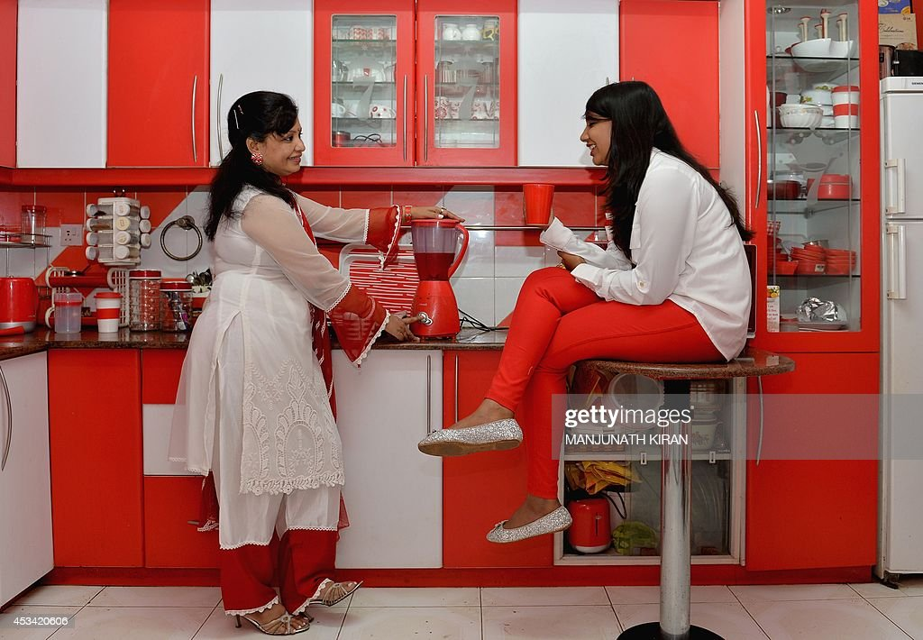 In this photograph taken on July 26, 2014, 16-year-old Maneesha (R) and 42-year-old Pushpa, respectively the daughter and wife of Indian businessman Sevenraj , who has a fixation for the colours red and white, share a conversation in the kitchen at the family's residence in Bangalore. 52-year-old Sevenraj's fetish for red and white colours started several decades ago with an intention to create a unique identity for himself and a brand image for his real estate agency went on to become a part and parcel of his life, his home and his family. Born as the seventh offspring, his realist father named him 'Sevenraj' and thus the number '7' too has remained his other fixation apart from the 'Red & White' colours. Everything in his house, office, his car are of the two shades. His family dress in red and white too when they go out with Sevenraj. AFP PHOTO/Manjunath KIRAN