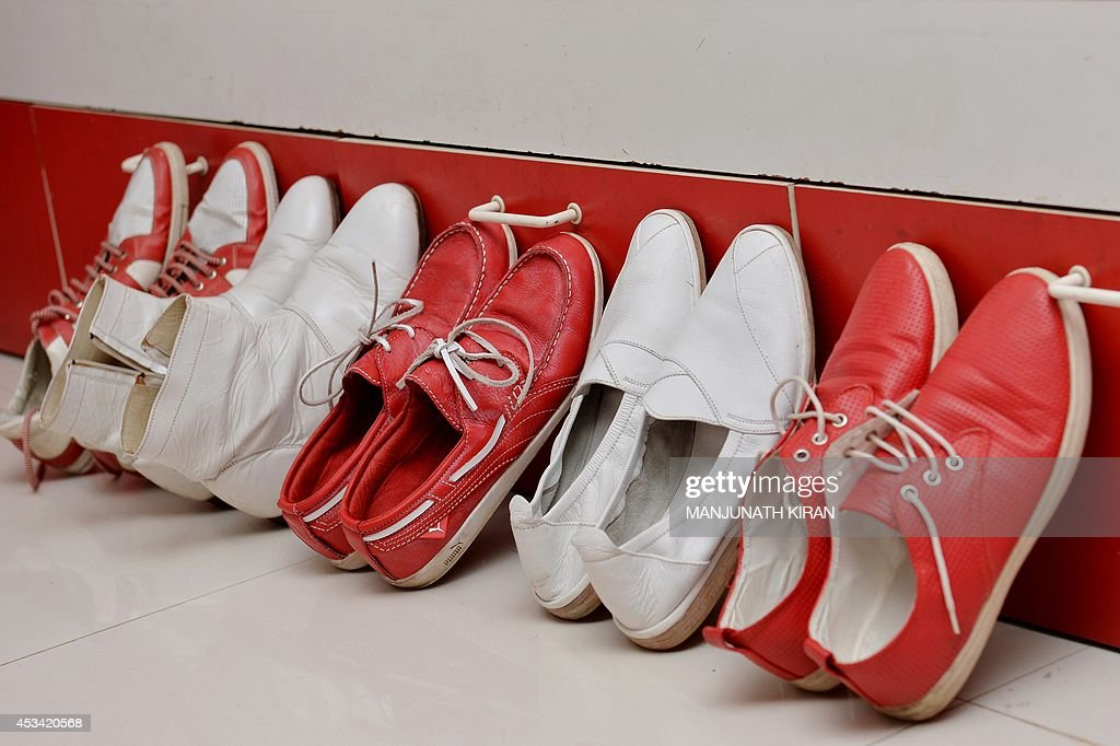 In this photograph taken on July 26, 2014, a collection of red and white pairs of shoes stand in row at the residence Indian businessman Sevenraj , who has a fixation for the colours red and white in Bangalore. 52-year-old Sevenraj's fetish for red and white colours started several decades ago with an intention to create a unique identity for himself and a brand image for his real estate agency went on to become a part and parcel of his life, his home and his family. Born as the seventh offspring, his realist father named him 'Sevenraj' and thus the number '7' too has remained his other fixation apart from the 'Red & White' colours. Everything in his house, office, his car are of the two shades. His family dress in red and white too when they go out with Sevenraj. AFP PHOTO/Manjunath KIRAN