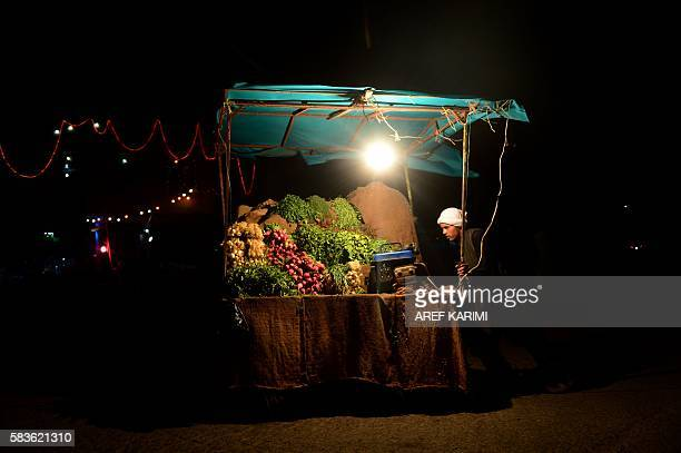 TOPSHOT In this photograph taken on July 26 an Afghan fruit vendor waits for customers at a roadside stall in Herat / AFP / AREF KARIMI