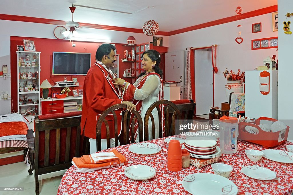 In this photograph taken on July 26, 2014, Indian businessman Sevenraj (L) who has a fixation for the colours red and white has his tie adjusted by his wife Pushpa at their residence in Bangalore. 52-year-old Sevenraj's fetish for red and white colours started several decades ago with an intention to create a unique identity for himself and a brand image for his real estate agency went on to become a part and parcel of his life, his home and his family. Born as the seventh offspring, his realist father named him 'Sevenraj' and thus the number '7' too has remained his other fixation apart from the 'Red & White' colours. Everything in his house, office, his car are of the two shades. His family dress in red and white too when they go out with Sevenraj. AFP PHOTO/Manjunath KIRAN