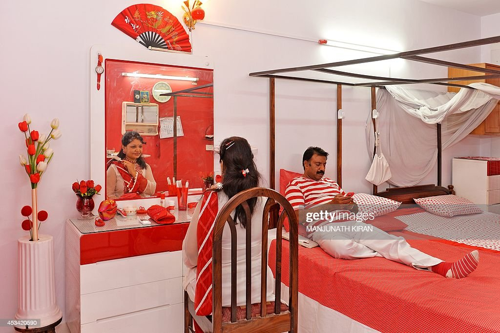 In this photograph taken on July 26, 2014, Indian businessman Sevenraj (R) who has a fixation for the colours red and white relaxes with his wife Pushpa at their residence in Bangalore. 52-year-old Sevenraj's fetish for red and white colours started several decades ago with an intention to create a unique identity for himself and a brand image for his real estate agency went on to become a part and parcel of his life, his home and his family. Born as the seventh offspring, his realist father named him 'Sevenraj' and thus the number '7' too has remained his other fixation apart from the 'Red & White' colours. Everything in his house, office, his car are of the two shades. His family dress in red and white too when they go out with Sevenraj. AFP PHOTO/Manjunath KIRAN