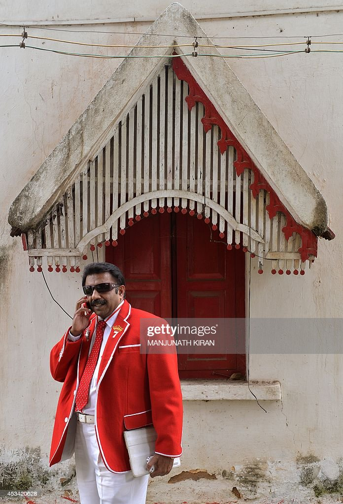 In this photograph taken on July 26, 2014, Indian businessman Sevenraj who has a fixation for the colours red and white speaks on his cellular telephone outside his office in Bangalore. 52-year-old Sevenraj's fetish for red and white colours started several decades ago with an intention to create a unique identity for himself and a brand image for his real estate agency went on to become a part and parcel of his life, his home and his family. Born as the seventh offspring, his realist father named him 'Sevenraj' and thus the number '7' too has remained his other fixation apart from the 'Red & White' colours. Everything in his house, office, his car are of the two shades. His family dress in red and white too when they go out with Sevenraj. AFP PHOTO/Manjunath KIRAN